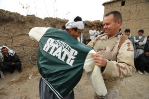 U.S. Air Force Colonel Victor Kuchar helping an Afghan man into a new jacket